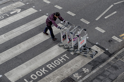 A trolly wrangler heards luggage trollies at Hong Kong International airport on a cold grey day