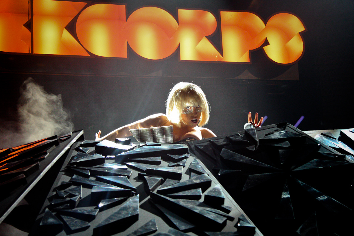 FROM THE ARCHIVE: Lady Gaga at Orange RockCorps, Manchester Apollo, 2009 by Ash (photo © Ashley Bird 2009) This was my first really major concert shoot. I'd recently begun shooting for Orange RockCorps - an organisation which recruits (mostly) young people to do community work in return for tickets to concerts. Lady Gaga was new on the scene but already causing a huge stir with Poker Face and Just Dance. My first job for RockCorps had been to take photos of her visit to one of the community projects - volunteers helping paint and clean up the HQ of Body Positive, an HIV support group in Manchester. She had turned up with her hair woven into a sort of huge button. (At the time this seemed pretty outlandish, but now that seems like a pretty conservative sartorial choice for her.) Gaga then went on to headline the RockCorps concert at the Apollo, and I was really excited to be in the photo pit. I think she planned the set opening with her now well-known senses of irony and theatre. Most of the photographers were only allowed to shoot the first song… that song was Paparazzi… and she was shrouded in darkness and/or dry ice for much of it. I found it pretty funny, but only because as RockCorps' official photographer I was allowed to shoot the whole set. I was really pleased to see I got some decent shots from that first song though (so if I HAD only been allowed to shoot that, I wouldn't have been screwed). This one was actually right at the beginning, as she emerged from beneath a pulsating mound of these dalek-like panels, and just caught the light in an interesting way. There's a name for those panels, but I can't remember what it is. Anyone? Anyone? Bueller? Bueller? The rest of the set was amazing. Being up close to a performance like that - with her four costume changes (in a roughly 30 minute set if I remember correctly), the dance routines and lighting all giving me plenty to shoot - was a real privilege. I could also see from that close just how hard she works on stage. It really puts lazy stool-bound boy bands to shame. And she definitely sings live through all of it.  I do love my rock, metal, indie and folky sorts of music, but sometimes you can't beat a good pop concert for photography opportunities. And let's face it, Gaga's the ultimate pop experience right now… POSTED BY ASH