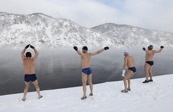 Divnogorsk, Russia Members of a winter swiming club warm up on the bank of the Yenisei river in an air temperature of about -25C (via guardian.co.uk)