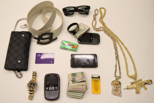 "The Things I Carry: 2 Chainz via The FADER Editor's Note: Interesting setup there. I notice your wallet has a chain, which is a good idea to maintain maximum retention, especially if you are particularly conspicuous about how much money you have on you at any given time. With that said, it seems the wallet size, despite being at the maximum size for comfortable pocket carry, is insufficient for holding all of your cash. Judging by your method of retaining cash (such as rubber bands or friction and gravity) I would suggest investing in a larger moneyclip (perhaps the Superiortitanium Viper would serve you well) or even a small to medium-sized satchel with a $ symbol on it. They say time is money, and you have plenty of it, so it's good that you wear a watch to manage all of that. I like the extra large lighter too — it should last longer at the expense of pocket space, but perhaps you have more to work with than the average EDCer. I must applaud your abundance of backups. You have not one, not two, but three phones because when there's an app for everything, who needs tools? Lastly, it's most evident that you subscribe to the ""two is one; one is none"" adage with your dual-chain carry (and even moreso reflected in your name). While nice pieces, I would say your firearm would not be the most effective in self-defense despite being easily accessible as a necker."