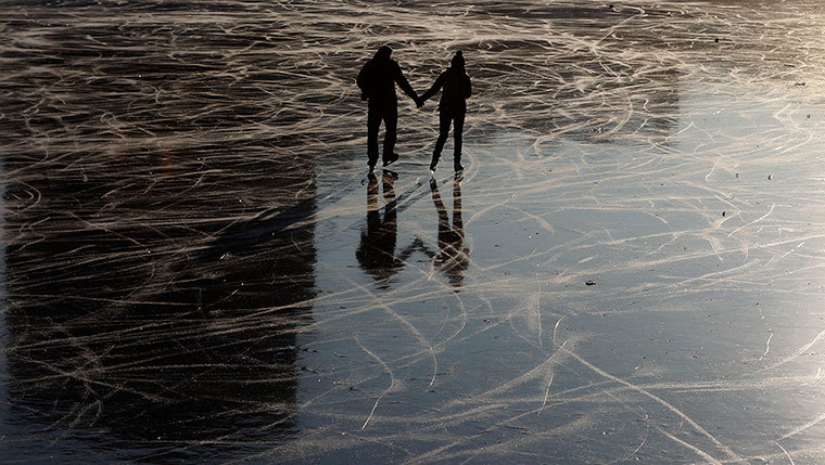 Prague, Czech Republic A young couple skate on a frozen pond (via guardian.co.uk)