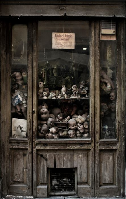 Shop window of a dolls hospital, Rome, Italy. The dolls are repaired and the damaged parts have been thrown into a window to gather dust.