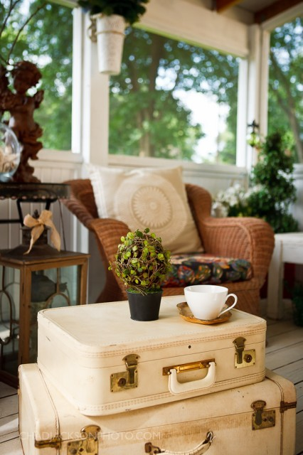 A sweet cottage porch is decorated with comfy wicker furniture and vintage suitcases (via Chad Jackson Photo)