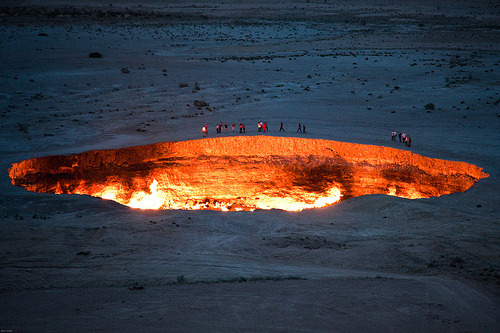 aneverendinglovesong:   Derweze, also known as the door to hell, is a 70 meter wide hole in the middle of the Karakum desert in Turkmenistan. The hole was formed in 1971 when a team of soviet geologists had their drilling rig collapse when they hit a cavern filled with natural gas. In an attempt to avoid poisonous discharge, they decided to burn it off, thinking that the gas would be depleted in only a few days. Derweze is still burning today   Holy shit I NEED to see this.