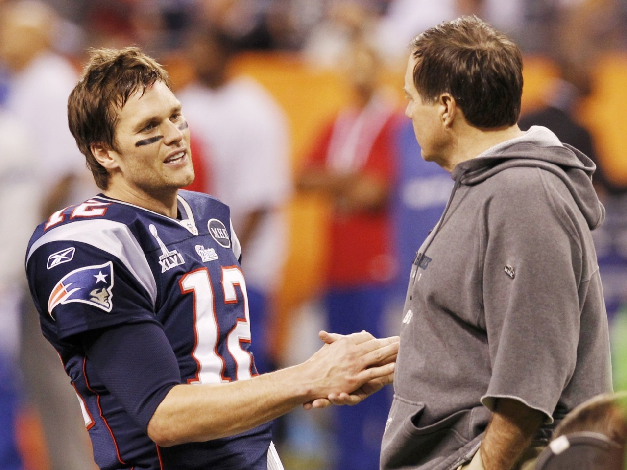 New England Patriots quarterback Tom Brady (L) shakes hands with Patriots head coach Bill Belichick before their team plays the New York Giants in the NFL Super Bowl XLVI football game in Indianapolis, Indiana, February 5, 2012. [REUTERS/Mike Segar] Read and participate in the Super Bowl XLVI live blog on Reuters.com