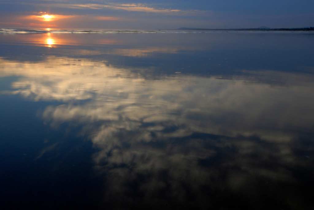 The sun and clouds are reflected on the calm water in Solanas, Punta del Este, Uruguay.