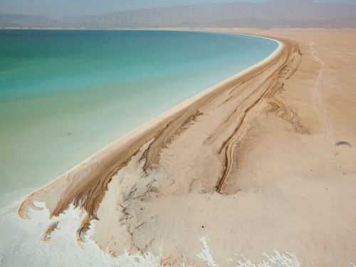 nationalgeographicdaily:  Lake Assal, DjiboutiPhoto: George Steinmetz Djibouti's Lake Assal is one of the world's saltiest lakes. Intense heat and strong winds fuel rapid evaporation, leaving a bathtub ring of minerals around the lake's shore.