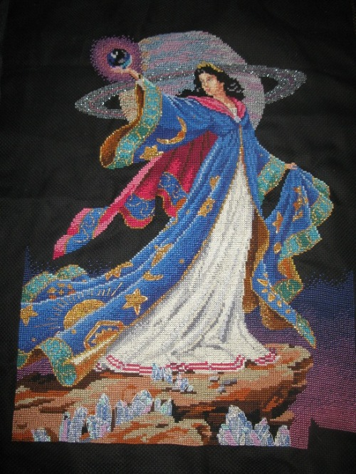elfmagick:  another thrift shop find, is this piece of cross stitch that someone quite obviously put so much fucking work into..  and i'm so thoroughly baffled by what the cross stitch is actually showing..  some sort of magick wizard woman on another planet that happens to be close to saturn, waving a crystal ball around surrounded by crystals?  i can get behind that. though i really doubt whoever spent countless hours making this, wanted it to end up sewn onto a filthy faery's coat..  but alas such is life.