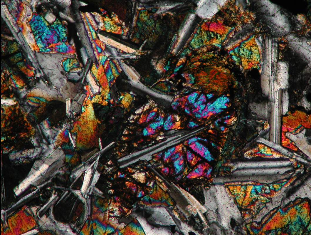 alexadventure:  quartz crystals in polarized light, shot through a gypsum filter to shift the wavelengths down the Michel-Levy color chart.