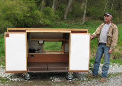 mobile single-person homeless shelter, designed and built by paul elkins complete with bed, kitchen, storage, window display, cooler, washroom and rain catcher via designbloom
