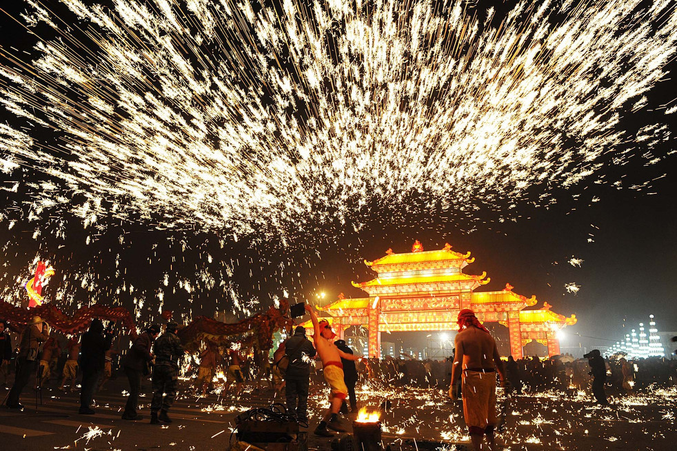 Under a shower of sparks from fireworks, people perform the dragon dance during a celebration of the Lantern Festival at a park in Chongqing, China in southwest China,Monday, Feb. 6, 2012. ZUMA24.com Chen Cheng