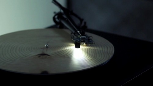 "This Record Player Turns Trees Into Music  Designed by German artist Bartholomäus Traubeck, this one of a kind  record player revolutionizes the classic vinyl playing turntable. By  using circular cross-sections of trees rather than vinyl records, the ""Years"" player gives us an idea of what music would sound like if mother nature  was a composer. As one might expect from a chopped down tree, the music  is fairly dark and ominous. Unlike traditional turntables,  the Years player utilizes a digital camera and light where you would  normally find the needle. As the turntable rotates a circular piece of  wood, the light and camera scan the rings of the wood for information  such as growth rate, texture, thickness and overall color tone. The data  is then sent through custom computer software that maps the data and  transforms it into a musical scale played with the sounds of a piano. Although it would be silly to expect the music to match the quality of a famous classical composer, the resulting tones actually sound surprisingly good. Because  of the way the software was written, Traubeck states that there are  some clear rules the player must follow, but each tree slice is  different enough to give off its own unique sound.  [video here]"