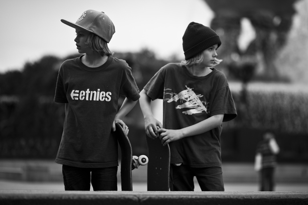 Twins with skateboard, and hats.