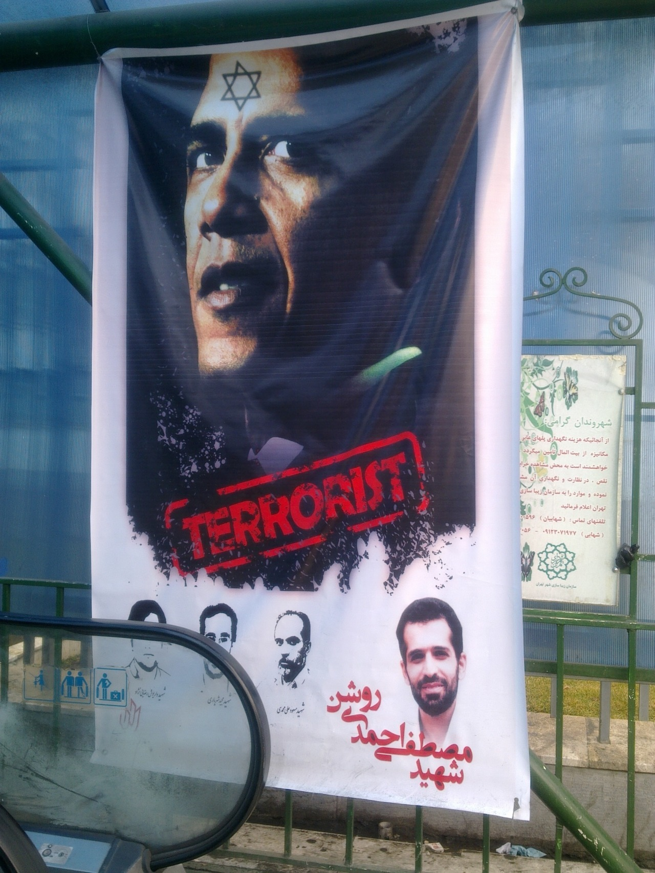 motherjones:  Obama poster on the streets of Tehran. (via)  The worst part is that Obama did this tattoo in the mirror, so it's backwards.