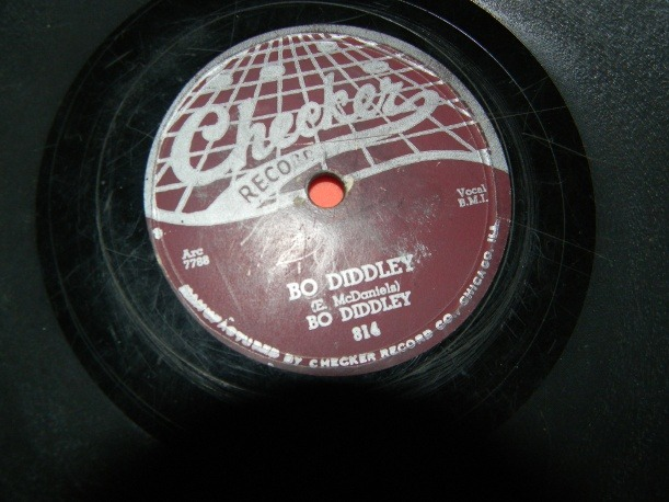 Bo Diddly  Bo Diddly/I'm a man  Shelac/Clay 78 RPM single. Circa 1955.  This is one of my favorite pieces from my personal collection. Pressed into a remarkably brittle clay, this is the quintessential song of early rock and R&B.  I've been sitting on this one for a while. I picked it up a few years ago at an estate sale, because it was too awesome to pass up, but I've never owned a record player that was designed for playing 78s. I've still got it. I've only listened to it twice, the first time shortly after I purchased it, the second time last night as I recorded audio samples using a friends turntable. To be frank, it was amazing. 78s sound… just different. What they lack in fidelity they make up for in character, in force. They transform familiar songs into something wholly other.  On the table we used it played through without skipping. It was a bit noisy, but that is the way of these things. As I said, I've recorded some audio samples, and I will post them soon.  I honestly don't want to get rid of it. I'm even less inclined to upon hearing it again, but I can't justify keeping it without the ability to listen to it.I'm planning on selling it, but I'd like to avoid eBay and the like.  It's a really cool, and rather obscure find, and I thought I'd give the folks here at tumblr the first crack at it.  I'm asking $50 for the record, plus shipping. We can handle payment through paypal or google checkout.  More photos (and an audio sample) available upon request.  And if my advertising has offended your delicate sensibilities, let me know that too. I don't want to alienate any of my followers.