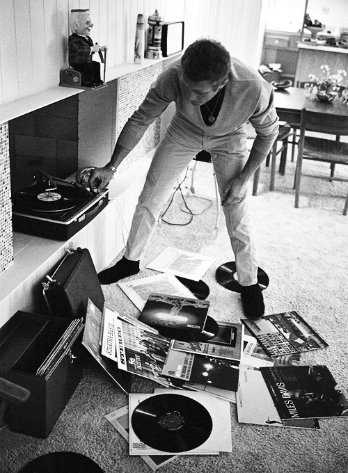 Steve McQueen plays records at home, 1963. Photo by John Dominis.