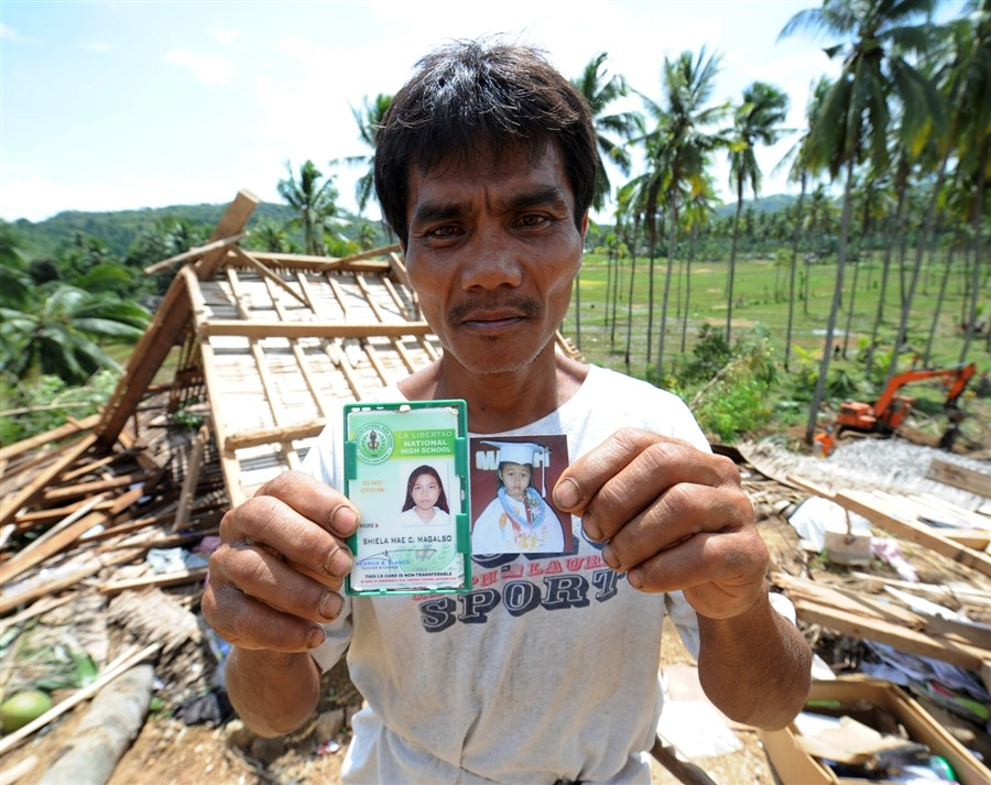 Primitivo Magalso shows the photo and ID of his missing children next to his destroyed house on the slope of a mountain which collapsed at the height of the powerful earthquake,in the village of Songgon, La Libertad town, Negros Oriental province, central Philippines on Feb. 8. Survivors of a deadly quake in the Philippines begged rescuers to keep searching for dozens of people buried in landslides, but officials said hopes of finding them alive were dim. [Credit : Ted Aljibe / AFP / Getty Images]
