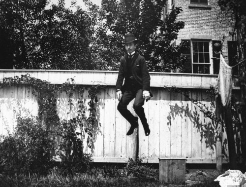 A man in a suit and bowler hat jumping in the air in his backyard. Photograph by Wallace G. Levison. Brooklyn, New York, 1890.
