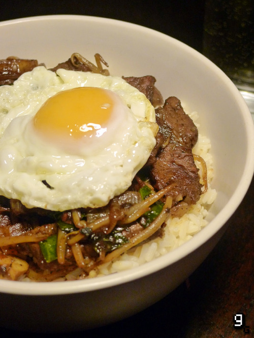 "Request: Persona 4 – Aiya Rainy Day Special Mega Beef Bowl  Back in the initial days of Gourmet Gaming I made the Steak Skewers from Persona 4. It was one of my earliest requests and the first popular post that seemed to strike something within the incredible Persona fan-base. I thought it was only fair that after a slew of new requests for the Aiya Rainy Day Special Mega Beef Bowl that I repay their kindness and revisit Persona 4 as a game that's helped make Gourmet Gaming what it is today. To be honest the thing that sold me on making this dish was the idea that this ""bowl is a portal to the meat dimension"". A meat. Dimension. Let's think about that for a moment… Do you think you have enough understanding, knowledge, courage and diligence to face this challenge? Click 'Read More' for the full recipe! [[MORE]]  This recipes serves 2. What you will need: A large wok, a frying pan and a large bowl. Ingredients: 250g / 1 Cup White Rice 500g / 17oz Frying Steak 4 Tablespoons Light Soy Sauce 1 Teaspoon Cornflour 2 Tablespoons Olive Oil 2 Teaspoons Sesame Oil 100g / 1 Cup White Onion (Sliced) 1 Teaspoon Garlic 1 Teaspoon Fresh Ginger (Grated) 1 Teaspoon Red Chilli (Chopped) 2 Teaspoons Chinese Five Spice 200g / 1 Cup Brown Chestnut Mushrooms (Quartered) 50g / 1 ½ Cup Pak Choi (Sliced) 150g / 2 Cups Bean Sprouts 2 Teaspoons Dark Soy Sauce 250ml / 1 Cup Beef Stock 1 Egg Preparations: Boil the rice as per the instructions; usually 1 part rice to 2 parts water. Slice the steak into strips and place them in a bowl. Add the light soy sauce, cornflour and mix well. Leave the beef to marinate for about 15 minutes. Making the Aiya Rainy Day Special Mega Beef Bowl: On a high heat, heat the wok then pour in the olive oil and sesame oil. Add the beef and fry until browned (about a minute or two) then remove from the wok and set aside. Add the onions to the wok and fry them until soft. Add the garlic, red chilli, ginger, Chinese five spice and lightly fry. Add pak choi, bean sprouts and mushrooms and stir fry for several minutes. Once lightly cooked return the beef to the wok. Pour in the beef stock and dark soy sauce. Allow the mixture to reduce for about 5 minutes. Heat a little oil in a separate frying pan and fry the egg until lightly crispy, then remove from the pan and set aside for later. Feel free to poach the egg or leave it raw for authenticity. By now your rice should be cooked; spoon the rice into a bowl then layer on the beef and top with the egg. You're now ready to face the Aiya Rainy Day Special Mega Beef Bowl Challenge!  You can also make a vegetarian version of this dish by replacing the beef with tofu and the beef stock with vegetable stock. I don't know if it's because it was 11PM by the time I got to eat this after a horrible mix up with my food delivery or if it actually is one of the best things I've ever tasted. Either way this wasn't much of a challenge for me as I practically inhaled the dish. I've had egg fried rice before, but I had no idea how awesome a fried egg on top of a stir fry would be - all this time I've been missing out! It's a rich, spicy and sweet dish that would, funnily enough, be a perfectly reinvigorating meal on a cold or rainy day. So the next time it rains, why not make this dish and set yourself a challenge of your very own! It's sure to improve some aspects of your personality (your friends can thank me later). Aiyaaaaa! Like this? You might also enjoy the Persona 4 - Steak Skewers."