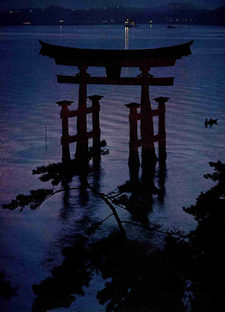 Guardian gateway, the torii entrance to Itsuku Shima Shrine shelters a sacred corner of Hiroshima Bay from the lights of change that multiply along the shore. Much of Japan wears a new face, but in many villages and island byways of the Inland Sea, the grace and traditions of the past stubbornly linger on. National Geographic, December 1977