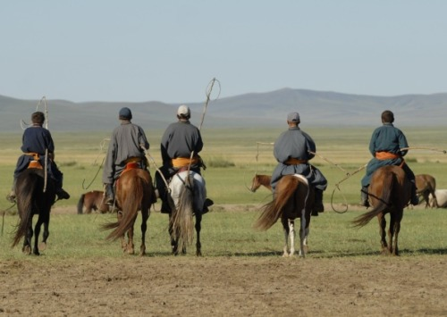 Mongolians on horseback with uurgas - wooden lassos for catching troublemaking livestock. Photo by Julia Horton.