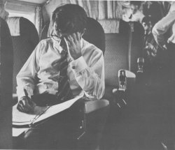 Bobby Kennedy jots down a few notes while on a flight