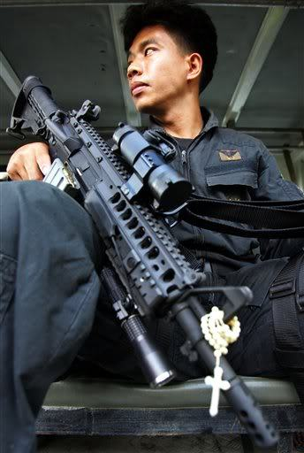 gunrunnerhell:  Filipino soldier with a custom AR (Has the very distinct ARMS S.I.R quad rail system. I've always liked the look of that rail but it's fairly old now and many prefer a lighter alternative. Note the rosary wrapped around his rifle's front sight.)