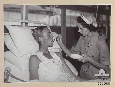 1945-04-18. PRIVATE J. MCDONALD, AUSTRALIAN ARMY MEDICAL WOMEN'S SERVICE  (2) FEEDING GUNNER H. HARTE, 554 LIGHT ANTI-AIRCRAFT BATTERY (1), A  PATIENT AT 2/1 GENERAL HOSPITAL, WITH ICE CREAM WHICH IS MANUFACTURED AT  THE HOSPITAL.