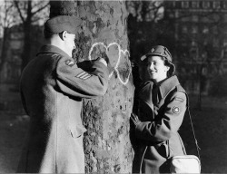 maudelynn:  Young couple chalking hearts onto a tree. Valentine's Day, 1944