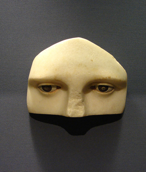 immaginaria:  Upper part of a marble face. From the Asklepieion in Athens. Around 350 B.C.On the eyebrows and the inner part of the eyelids some traces of red pigment survive. The iris is of brown, the pupil of grey stone. The eyeball and the inner part of the corner of the eye are rendered in white and red stone respectively. The head was fastened into a poros block which had niches of various sizes for inserting the votive gifts. The inscription carved on the poros block informs us that it was an offer of Praxias to Asclepius for healing his wife. (photo Michael Tziotis)