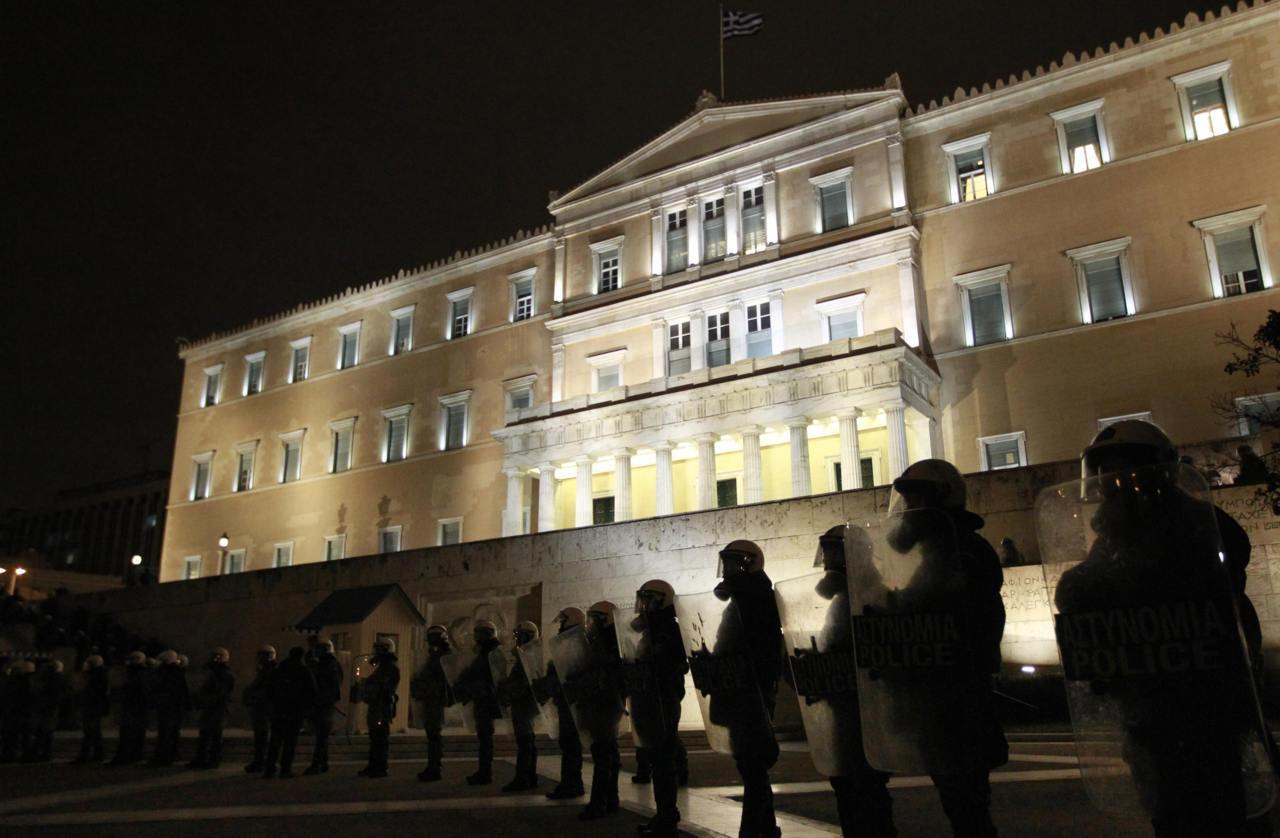 Riot police stand guard in front of the parliament during a protest against austerity measures in Athens February 9, 2012. Greece's two major labour unions called a 48-hour strike for Friday and Saturday against the reforms. [REUTERS/John Kolesidis]
