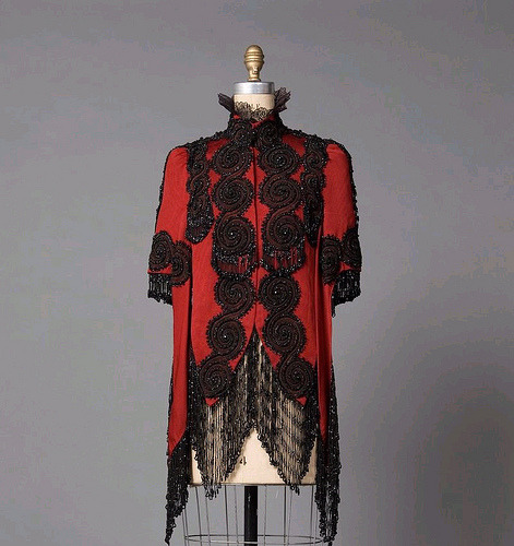 c. 1887 Met Red bengaline mantle, it's waist length in back and nearly knee length at front.Just like a cape, it just wraps around the arms, but there is also an extra length of material at the front of the sleeve. It has been beaded with black jet and large spiral circles cover the front and back and around bottom. The collar frill is of horsehair lace