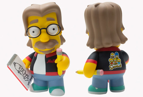 "kidrobot x Matt Groening vinyl toy  ""…Created by legendary ""Life is Hell"" cartoonist Matt Groening, THE SIMPSONS is celebrating its 500th episode in February 2012, and Kidrobot is honoring the father of primetime animation in the only way we know how: making him into a 6-inch vinyl toy! Complete with goatee and glasses, director's jacket, and pad and pencil accessories, it is the first EVER Simpsons Matt Groening toy…"" —kidrobot"