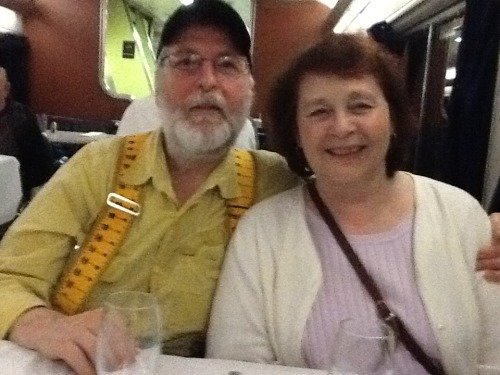 Wayne and Joyce from Chaska, Minnesota Wayne is ready with the answer when I ask him about the suspenders, and it's not any where near what I expected.  He is using the wide, comfortable suspenders to hold up a colostomy bag — the result of three operations for colon cancer. At one point, not sure of the timing, he was told to arrange hospice care!  Didn't need it. Since then he has stopped chemo treatments. Both he and Joyce are following a diet based on blood type — this, they say, is the reason Wayne is still alve, and on a train trip today. And yes, Wayne did work as a carpenter.