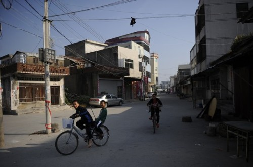 Children ride their bikes through an empty street in Wukan, a fishing village in the southern province of Guangdong on December 18, 2011. (via Photo from Getty Images)