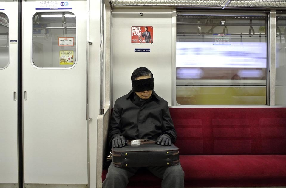 A man covered his eyes and took a nap as he rode a subway train in  Tokyo Thursday. Taking naps during commutes is relatively common among  the Japanese.