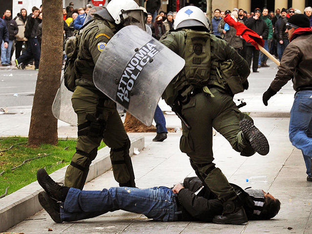 troposphera:  A police officer kicks an anti-austerity protester during clashes in Syntagma Square Photograph: Reuters