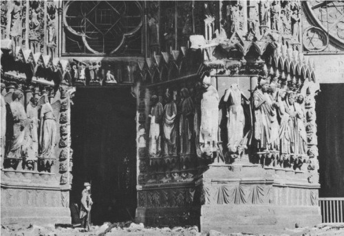 A soldier standing before the damaged west doorway of the cathedral at Rheims, France (http://www.gwpda.org/photos/)