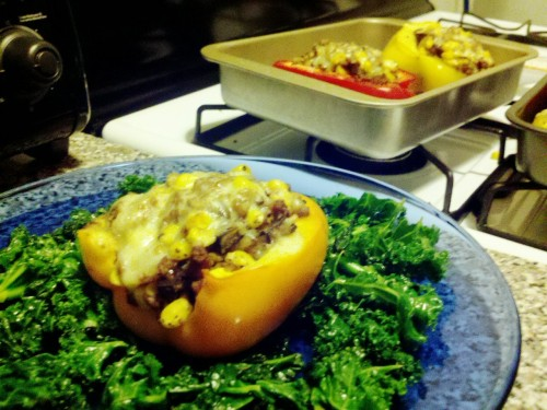 "Amazing home-made veg din! Bell papers stuffed with onions, veggie ""beef"" crumble, mushrooms, corn,  topped with cheddar cheese on a bed of sauteed kale"