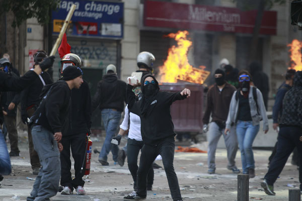 A protester throws a stone at riot police during clashes in Athens.