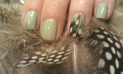 All nails in a light minty green, including one feather accent nail.