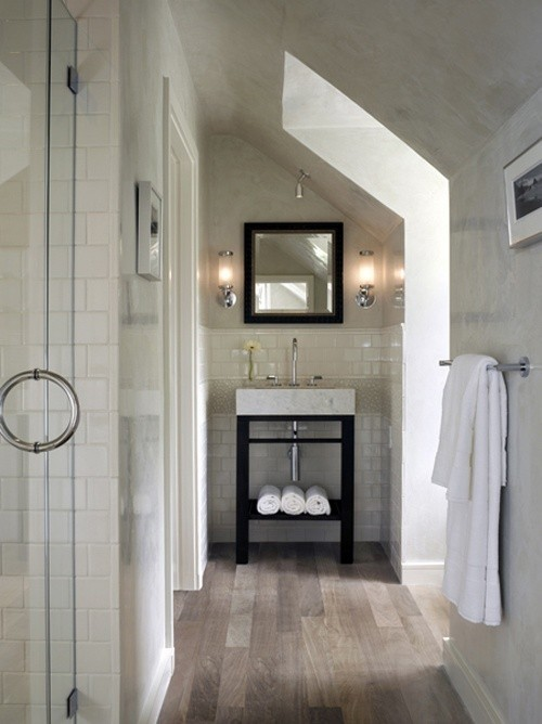 Contemporary bathroom with subtle hardwood floors. I love the small vanity. The open shelving for towels gives it a spa feel. I also like the use of space. Looks like it is built in the eaves. Follow CollegeGuyDesign if you like things like this showing up on your dash!