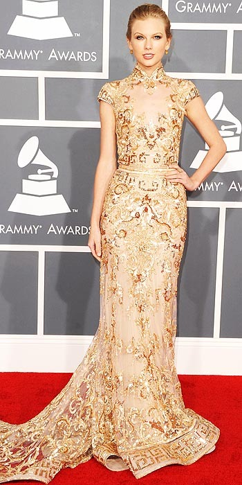 Taylor Swift at the Grammy Awards Taylor went with sparkle - which seems to be the trend of the night - in a high collared gold dress by Zuhair Murad.