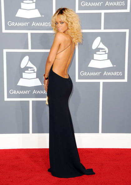 "Red Carpet Glam! Rihanna, 2012 Grammys Style Notes — Due to the overwhelming amount of re-tweets on Twitter as well as nonstop ""oohs and aahs"" about Rihanna's gorgeous black dress, it's no secret that the 23-year-old blonde bombshell was a show-stopper on the Red Carpet. Rihanna wore a simple yet sexy custom Giorgio Armani gown with a plunging neckline that was to-die for. But furthermore, the back of the dress was nothing but a hit. J'adore!"