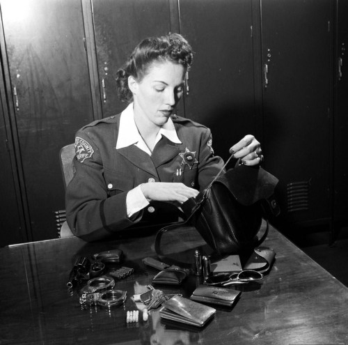A female police officer emptying the contents of her bag. Photograph by Peter Stackpole. Los Angeles, California, November 1950.