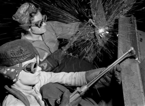 Female welders at work in a steel mill, replacing men called to duty during World War II. Photograph by Margaret Bourke-White. Gary, Indiana, USA, 1942.
