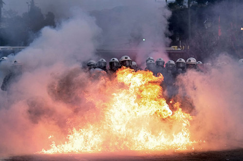 Greece austerity protests Thousands clashed  with riot police in Athens on Sunday as the Greek parliament approved  deeply unpopular budget cuts to secure a new eurozone bailout