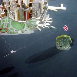 "Dunkin Island as imagined by Larry M Bogad, One of fifteen islands fabricated by Greg Sholette based on ideas proposed by invited collaborators, Mixed media (paper, sand, plastic, wire, resin), 2012 ""Dunkin' Island is a small island off of Battery Park, with a 100-yard diameter and round bulls-eye target standing at its center. A state-subsidized, comfortable water taxi will deliver those who have committed egregious offenses-for example, bankers and speculators responsible for the most recent financial crisis-to permanent exile on this island. A gigantic catapult that fires soft projectiles will be installed on the roof of the Museum of the American Indian, with open and free access to the public. Tourists and New Yorkers alike can aim and fire at the target on Dunkin' Island. The island is rigged with springs so that, when the target is hit, the entire mini-landmass submerges under water, bouncing back up again after the inhabitants have been thoroughly soaked."" - Larry Bogad Fifteen Islands for Robert Moses is a site-specific art infiltration into the Panorama of the City of New York, which was built for the 1964 World's Fair by urban planner Robert Moses and is now a centerpiece of the Queens Museum of Art. Artist and theorist Greg Sholette (co-curator of the ACFNY's current exhibition It's the Political Economy, Stupid) made and placed new islands about the Panorama's waterways, where they exist as silent, post-9/11 observers of the City's past, present, and future. On view through May 20, 2012"