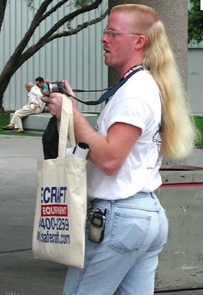 notmyvirginears:  ultimate mullet   The mullet, whitewashed jeans, tucked in t-shirt and grimy tote bag say 1988-1994. But that phone is 1999-2002 vintage. Maybe this guy just loves hideous objects from the recent past, and this is a current photo! How great would that be?