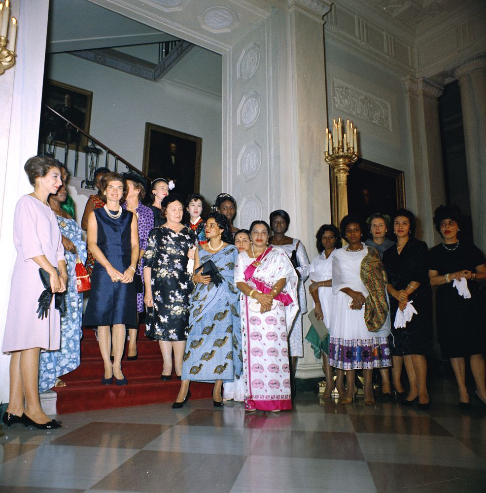 coolchicksfromhistory:  ourpresidents:  First Lady Jacqueline Kennedy hosts a tea party for wives of new ambassadors.  The guests stand in front of the grand staircase in the Entrance Hall of the White House.  Guests include: Neila Zouiten Bourguiba (wife of Ambassador Habib Bourguiba, Jr. of Tunisia); Mrs. Frédéric Guirma of Upper Volta; Mrs. Sergio Fenoaltea of Italy (first name unknown); Helena Drozniak (wife of Ambassador Edward Drozniak of Poland); Mrs. Michel Gallin-Douathe of Central African Republic; Seelawathie Rambukwella Gopallawa (wife of Ambassador William Gopallawa of Ceylon); Mrs. Matrika Prasad Koirala of Nepal; Nepalese interpreter Bhinda Malla; Mrs. Il Kwon Chung of South Korea; Mrs. Emmanuel Datnongo Dadet of Congo; Virginia Rusk (wife of Secretary of State Dean Rusk); Mrs. Ousmane Diop of Senegal; Mrs. Seydou Conte of Guinea.  Though it was the convention of the time, I really hate it when women are listed as Mrs. Husband's First and Last Name.  A quick google search suggests Mrs. Il Kwon Chung may be Park Hye Soo as that is the name given for his wife in this 1994 obit (although it may be a later marriage).